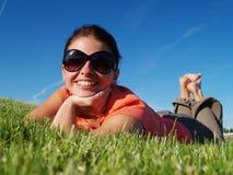 Flickan på ett gräs Arkivfoto