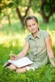 Flickan på ett gräs med boken Royaltyfri Foto