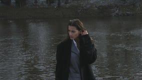 Flickan på floden i aftonen i det mörka ljuset