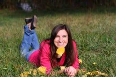 Flickan på gräset i hösten Arkivfoto