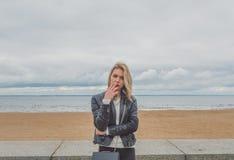 Flickan på granitinvallningen av en höstdag, rök royaltyfria bilder