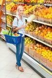 Flickan på lagret som väljer grönsaker, räcker kål arkivbilder