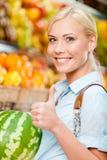 Flickan på marknaden som väljer frukter, räcker vattenmelon arkivbilder
