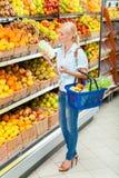 Flickan på marknaden som väljer grönsaker, räcker kål arkivbilder