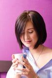 Flickan på morgonen sitter med koppen Arkivbild