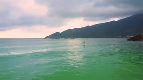 Flickan på paddleboard seglar längs kust som skummande vågor rullar på stranden stock video