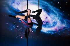Flickan på pylonen gör övningen mot bakgrunden av galaxen Royaltyfria Foton