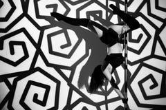 Flickan på pylonen gör övningen mot bakgrunden av svarta modeller Royaltyfria Bilder