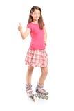 Flickan på rullskridskor som ger en tumme, ups Arkivfoto