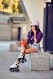Flickan på rullskridskormenknä i stads- parkerar Arkivbilder