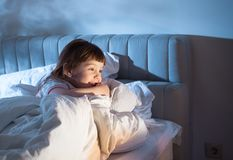 Flickan på sängen som skrattar och ser i den öppna dörren Royaltyfri Bild