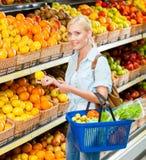 Flickan på shoppa som väljer frukter, räcker citronen royaltyfri foto