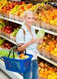 Flickan på shoppa som väljer grönsaker, räcker kål arkivbilder