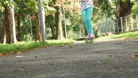 Flickan på skateboarden skjuter en fot och förbigår lager videofilmer