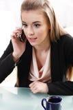 Flickan på skrivbordet som talar på Royaltyfria Foton