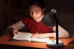 Flicka på skrivbordläsning en boka vid ljust av lampan Royaltyfri Fotografi
