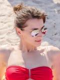 Flickan på stranden får brunbränd Arkivfoton