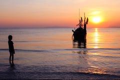 Flickan på stranden med en fiskebåt och en solnedgång Fotografering för Bildbyråer