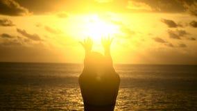 Flickan på stranden som tycker om solnedgången på ön av Bali En av den mest njutbara underhållningen på ön arkivfilmer