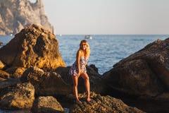 Flickan på stranden på vaggar på solnedgången i posera för klänning royaltyfria bilder