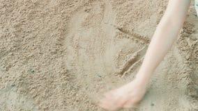 Flickan på stranden vid vattnet på sand drar arkivfilmer