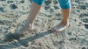 Flickan på stranden vid vattnet på sand drar lager videofilmer