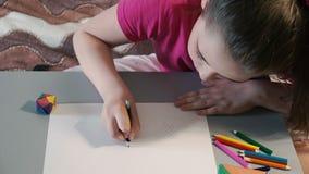 Flickan på tabellen drar i kulöra blyertspennor arkivfilmer