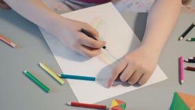 Flickan på tabellen drar i kulöra blyertspennor lager videofilmer