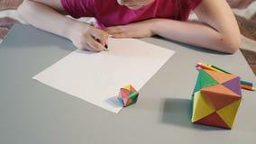 Flickan på tabellen drar i kulöra blyertspennor stock video