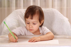 Flickan på tabellen och tecknar royaltyfri fotografi