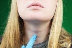 Flickan på undersökning på doktorn thyroid royaltyfri foto