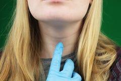Flickan på undersökning på doktorn thyroid royaltyfri bild