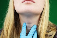 Flickan på undersökning på doktorn thyroid arkivbild