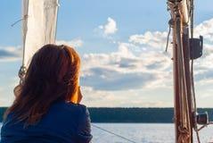 Flickan på yachten beundrar solnedgången arkivbild