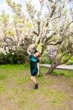 Flickan p? bakgrunden av en aprikos f?r blomma tr?d royaltyfria bilder