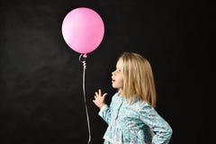 Flickan p? en svart bakgrund bl?ser en ballong arkivbild