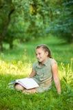 Flickan på ett gräs med boken Fotografering för Bildbyråer