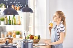 Flickan p? tabellen i k?ket med ett exponeringsglas av orange jui royaltyfria foton