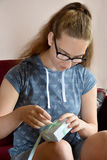 Flickan packar upp en gåva Fotografering för Bildbyråer