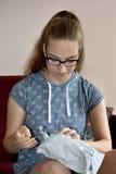 Flickan packar upp en gåva Royaltyfri Fotografi
