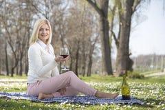Flickan parkerar in att dricka vin Arkivfoto