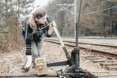 Flickan passerar manuellt pilarna på järnvägspåren Dagsljus d?r tonar arkivfoton