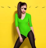 Flickan piratkopierar i grön bodysuit på den gula väggen med spikar bakgrund Royaltyfria Bilder