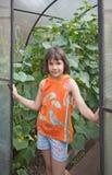 Flickan plattforer på ingången av växthuset Royaltyfri Foto