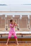 Flickan plays med vatten på däck av shipen. Arkivbild