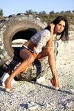 Flickan poserar på ett gummihjul Fotografering för Bildbyråer
