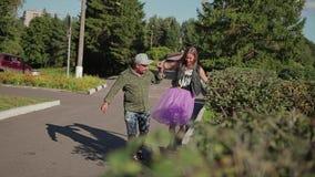 Flickan promenerar försiktigt trottoarkanten och kysser hennes pojkvän som rymmer hans hand skjutit trevligt stock video