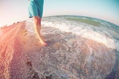 Flickan promenerar stranden Royaltyfri Foto