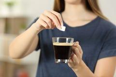 Flickan räcker att kasta en sockerkub in i en kaffekopp arkivfoton