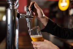 Flickan räcker att tjäna som ett halv literexponeringsglas av kallt och uppfriskande öl på en restaurang arkivfoton